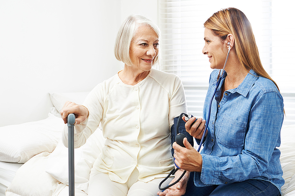 Caregiver doing blood pressure monitoring for senior woman at home